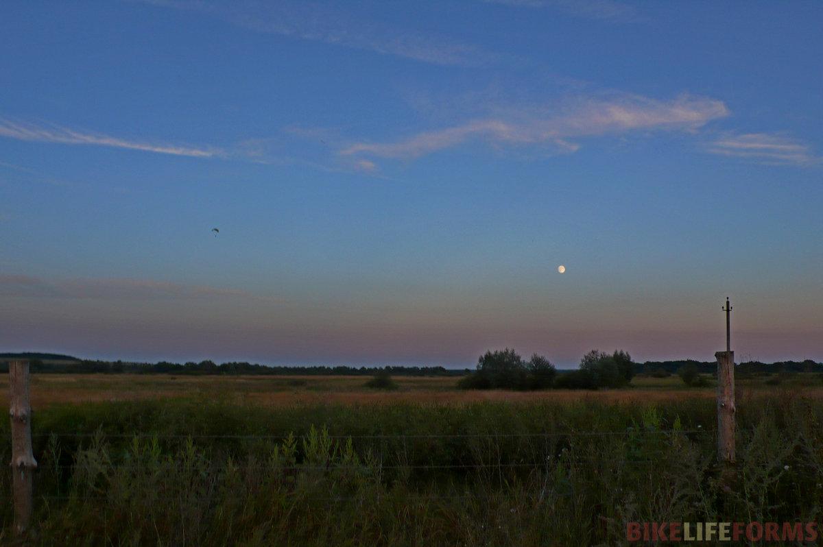 Всходит луна и одинокий странник неба на параплане летит к ней с желанием сорвать и положить себе в корзину словно лесной трофей.