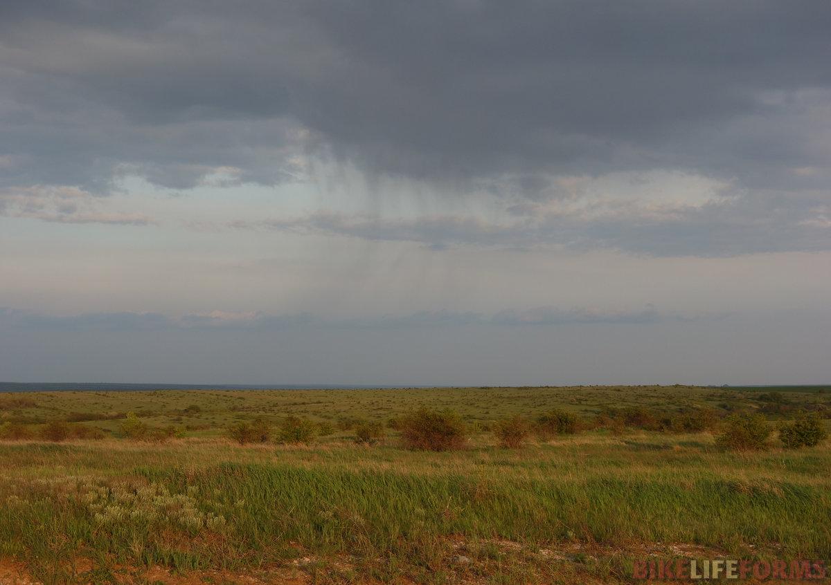 исчезающий дождь над предзакатной степью