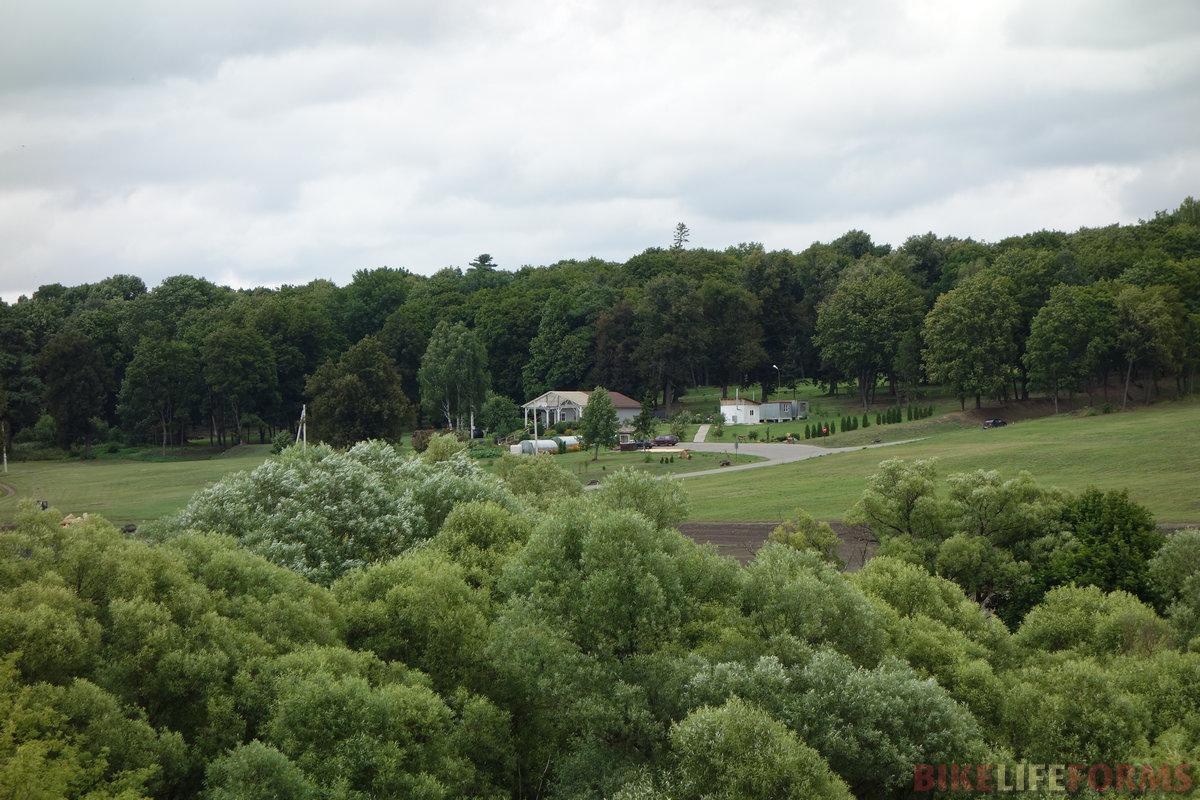 красивый парк на склоне. А внизу, у р. Любовши, родник с беседкой