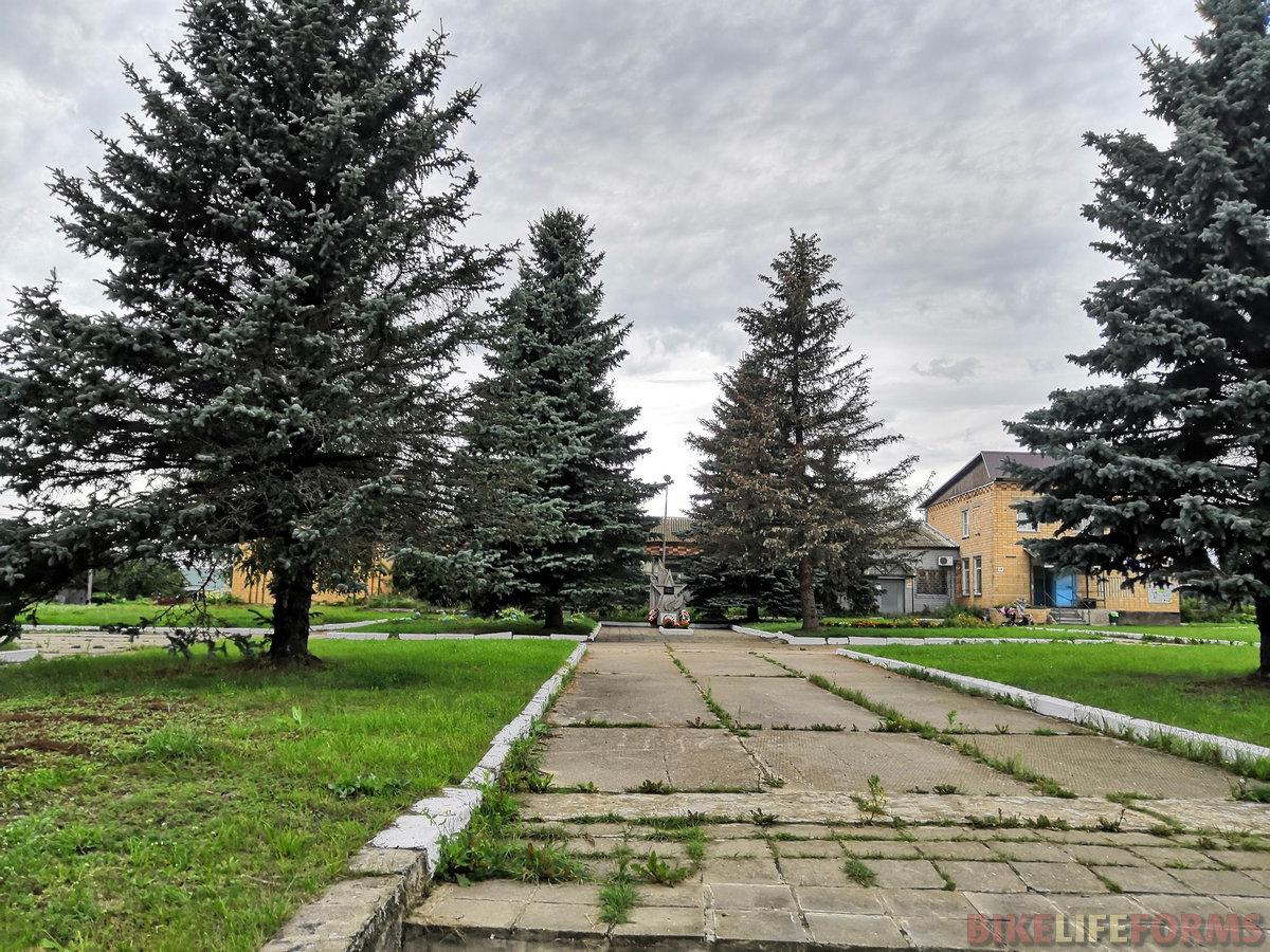 Некогда роскошная площадь в полузабытом поселке, видимо, бывшем центром колхоза. Сейчас природа потихоньку берет свое и разрывает стыки между бетонными плитами пучками зеленой травы.